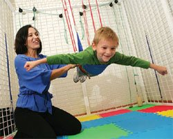 Maria Teresa Ferrer guides Aiden Roy, who has cerebral palsy,as he undergoes therapy with the Universal Exercise Unit.