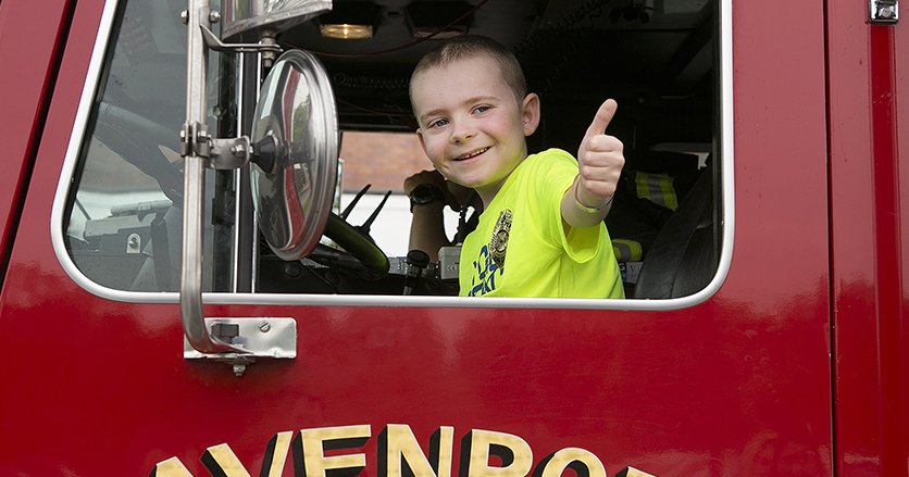 Alex Yule poses in a fire truck giving the audience a thumbs up