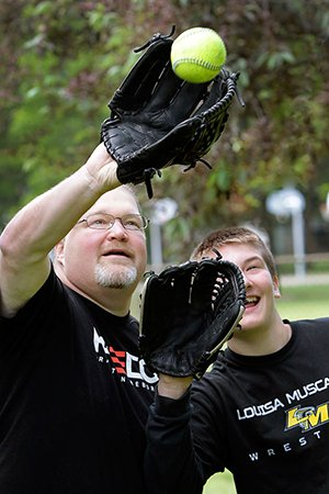Tom Mashek battles for a fly ball with his son Max, 13.