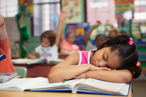 Girl fast asleep at her desk while at school