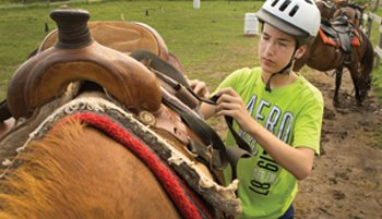 At his fourth year at Camp Genesis, Will Raun gets ready to ride a horse.