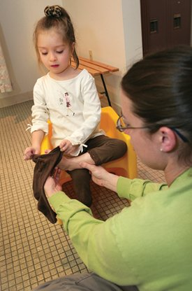 Madi improves her skills at getting dressed with occupational therapist Ashley Larson.