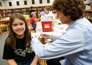 A student receives a free flu shot from the Flu Free Quad Cities Initiative.