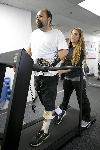 McGuirk works on a treadmill with his therapist
