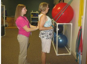 Elise, PT, assists a patient with postural exercises.