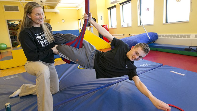 Ryland does a stretching exercise with Occupational Therapist Jenni Petersen