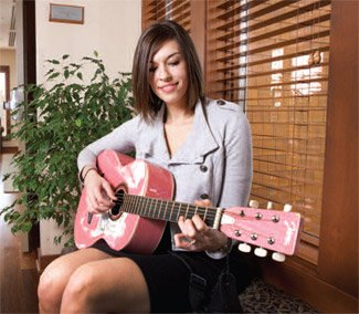 Music therapist Katey Krull plays her guitar at the Clarissa C. Hospice House in Bettendorf.