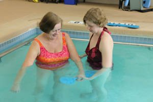 Cherie Blackwell, OT/R, CHT, is assisting Suzanne with aquatic upper extremity strengthening.