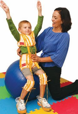 Maria Teresa Ferrer guides Aiden Roy, as he undergoes therapy with the TheraSuit.