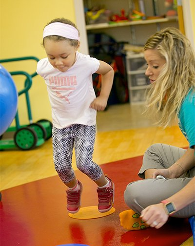Ivory participates in a jumping activity with the help of her therapist, Tess