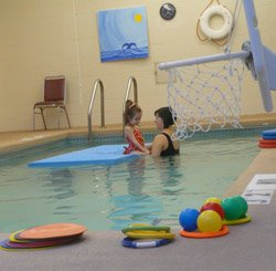 Katie Snyder, DPT, is working in the pool with Madi to address core stability and protective reactions.