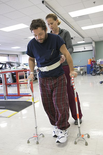 Using a walker, Jassen works his therapist on learning how to walk again