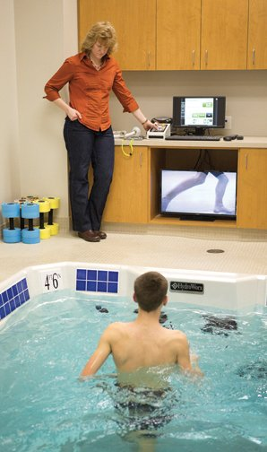 Runner Karson Sommer, Bettendorf, <br />uses the HydroWorx underwater <br />treadmill as physical therapist <br />Kathryn Ellsworth studies his gait <br />pattern on the video screen.