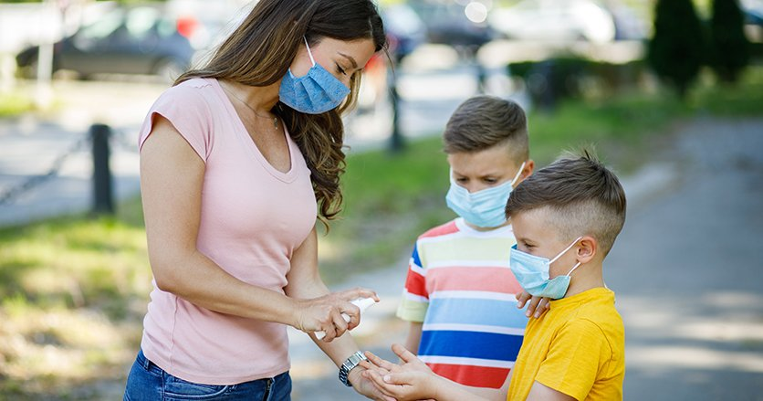 Mother and sons wearing masks and using hand sanitizer