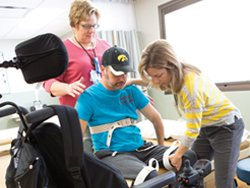 With the help of physical therapist Susan Bode, left, and physical therapy assistant Pam Glasgow, spinal cord injury patient Doug Taylor is learning to transfer himself from his bed to the wheelchair.
