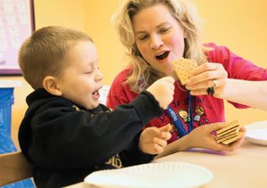 Tayden Bulten and occupational therapist Megan Long play a game with graham crackers at the Genesis Food School, held at the Genesis Pediatric Therapy Center in Bettendorf. Since coming to the school, Tayden has learned to eat peanut butter.