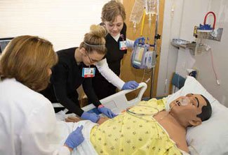 Nancy Ritter, RN, watches as Brittany Classen, RN, left, and Kelly Johnston, RN, right, insert an IV into a high-fidelity simulation mannequin in the new Genesis Learning Center.